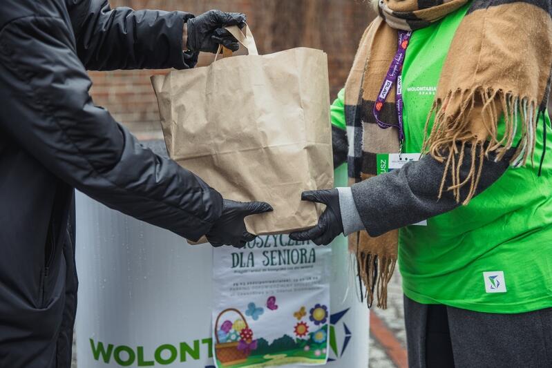 Zdjęcie przedstawia ręce dwóch osób: darczyńcy i wolontariusza. Jeden przekazuje drugiemu szarą papierową torbę z zakupami. Wolontariusz stoi po prawej, ubrany jest w zieloną koszulkę, oznaczającą uczestnika akcji
