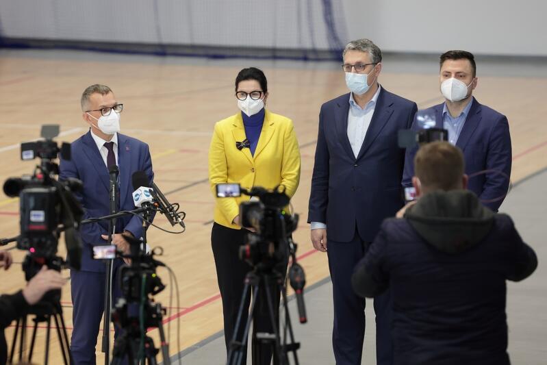 Cztery osoby stoją przed mikrofonami, trzech mężczyn w średnim wieku, w środku kobieta w żółtej marynarce