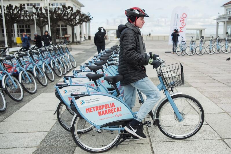 Plac przy molo w Sopocie, na którym w trzech rzędach stoi kilkadziesiąt niebieskich rowerów Mevo. Na pierwszym planie widzimy jak młody mężczyzna w kasku wsiada na jeden z rowerów. W tle widać drzew, kilka osób i biały pawilon przy wejściu na sopockie molo