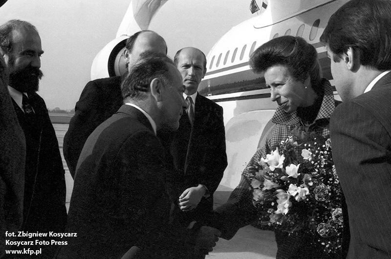 Elegancko ubrana kobieta w średnim wieku wysiadła właśnie z samolotu. W lewej ręce trzyma duży bukiet kwiatów. Witana jest przez kilku mężczyzn w garniturach. Prawą rękę podaje przewodniczącemu Rady Miasta Gdańska, Andrzejowi Januszajtisowi