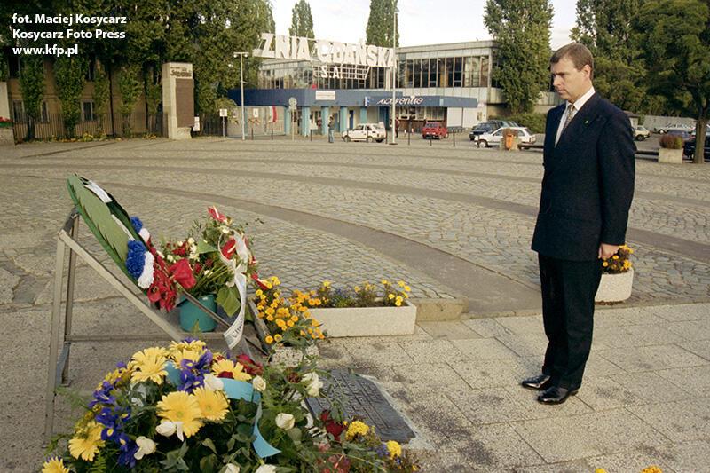 Młody mężczyzna stoi samotnie przed Pomnikiem Poległych Stoczniowców. Przed nim leżą złożone chwilę wcześniej kwiaty