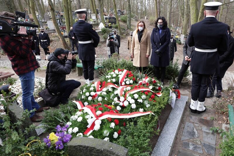 Grób przykryty biało-czerwonymi wieńcami i kwiatami. Przed grobem stoją dwie kobiety, twarzami do fotoreportera. Po prawej i lewej stronie grobu stoją uzbrojeni w karabiny żołnierze warty honorowej, pełnionej przez Marynarkę Wojenną RP. Obaj stoją plecami do obiektywu aparatu. Po lewej widoczny jest fotoreporter i kamerzysta, obaj robią zdjęcia pani prezydent i pani przewodniczącej. W tle są drzewa, pagórki i usytuowane na nich groby