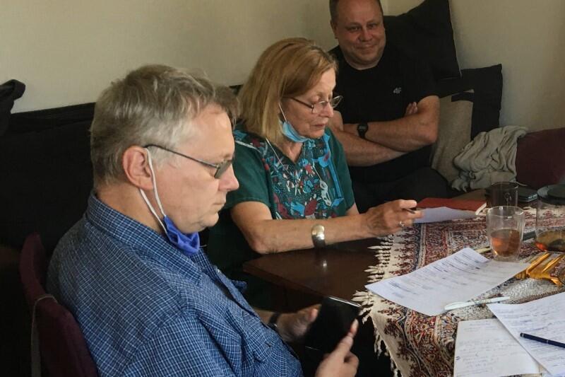 Po lewej widoczny jest mężczyzna w okularach i niebieskiej koszuli. Siedzi przy stole, znajdującym się po prawej stronie. Za mężczyzną, przy tym samym stole siedzi kobieta, ma blond włosy, okulary, ubrana jest w zieloną bluzkę z krótkim rękawkiem. Oboje mają przed sobą kartki z notatkami, kobieta trzyma jedną z kartek w dłoni i wczytuje się w tekst. W głębi zdjęcia, za obojgiem, siedzi uśmiechnięty mężczyzna z rękoma splecionymi na piersi - członek ekipy realizującej film