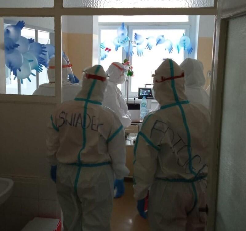 Fragment szpitalnej sali, na pierwszym planie stoją dwie osoby w kombinezonach medycznych