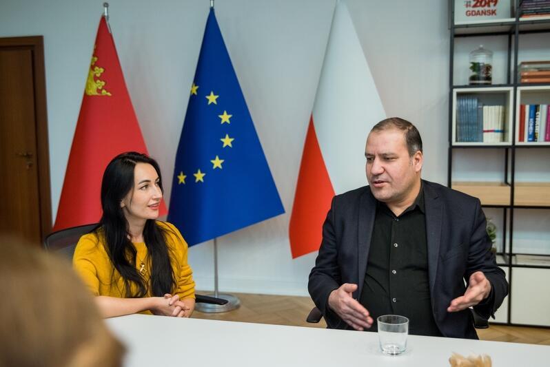 mężczyzna siedzi za stołem, gestykuluje podczas rozmowy, za nim widnieją trzy flagi: Polski Gdańska i Unii Europejskiej