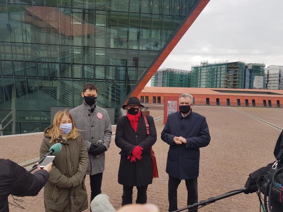 na zdjęciu widać czworo radnych, przed nimi jeden z mikrofonów dziennikarskich, a w tle widać szklaną fasadę budynku muzeum drugiej wojny światowej