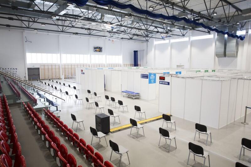 Hala sportowa. Po lewej widać trybunę z siedzeniami dla publiczności. W części środkowej i po prawej na zdjęciu widoczny jest parkiet do uprawiania dyscyplin sportowych. Na tym parkiecie w równych odstępach rozstawionych jest około 50 krzeseł dla osób szczepionych. Po prawej widać białe ścianki działowe - za nimi znajduje się zaimprowizowane w hali zaplecze medyczne