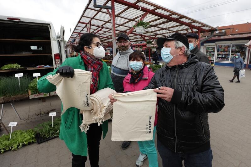Prezydent Dulkiewicz stoi po lewej stronie zdjęcia, trzyma naręcze lnianych toreb z niebieskim nadrukiem Gdańsk bez plastiku i rozdaje je mieszkańcom. Po prawej, tuż obok pani prezydent widoczne są trzy osoby: mężczyzna, kobieta i mężczyzna. Pan po prawej ubrany jest w brązową kurtkę ze skóry, z satysfakcją ogląda jedną z podarowanych toreb. Mężczyzna w szarej kurtce i kobieta w różowej kurtce przyglądają się tej scenie. Wszyscy mają maseczki