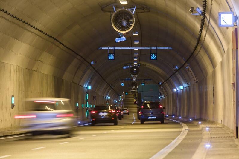 Wnętrze tunelu pokazane zza przedniej szyby jadącego samochodu. Widać auta, które są z przodu - wszystkie jadą w tym samym kierunku, po dwóch pasach jezdni. Sklepienie tunelu jest półkoliste. W szczytowym punkcie sklepienia podwieszony jest duży wentylator do usuwania spalin z tunelu