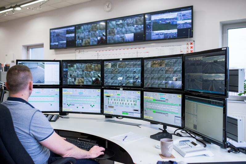Mężczyzna siedzi przy konsoli, przed nim znajduje się ściana monitorów, na których widać, jak odbywa się ruch w tunelu