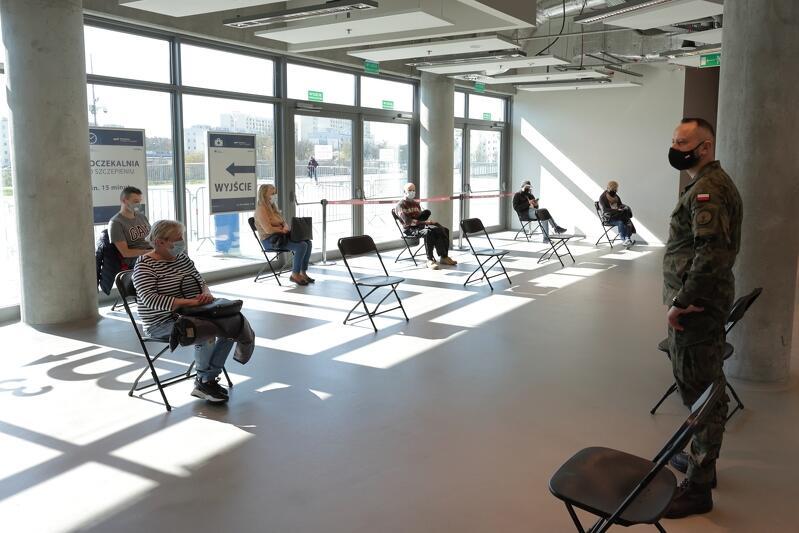 Krzesła, na nich siedzą osoby w różnym wieku