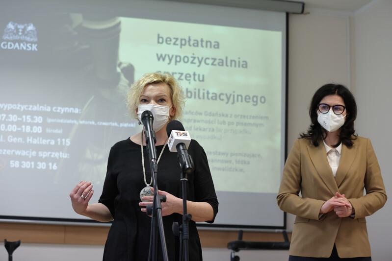 Mówi Małgorzata Niemkiewicz, dyrektor Miejskiego Ośrodka Pomocy Rodzinie w Gdańsku, w tle prezydent Aleksandra Dulkiewicz