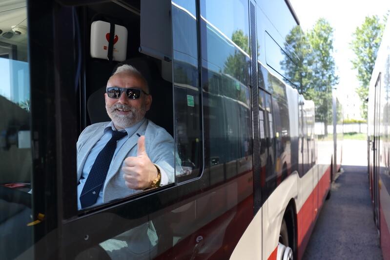Prawy bok miejskiego autobusu, pokazany od strony kabiny kierowcy. Jest lato, upał. Przez uchylony boczny lufcik widać twarz uśmiechniętego kierowcy w okularach przeciwsłonecznych. Ubrany jest w niebieską koszulę, ma granatowy krawat. Pozuje do zdjęcia trzymając w okienku zaciśniętą dłoń z wystawionym do góry kciukiem