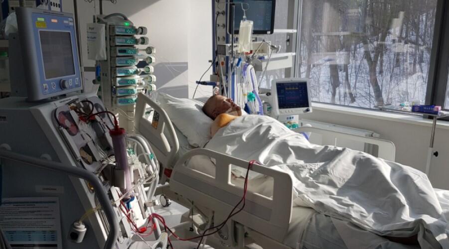 Sala szpitalna, łóżko, na nim leży przykryty mężczyzna