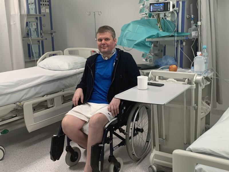 Mężczyzna w średnim wieku na wózku inwalidzkim, w szpitalnej sali