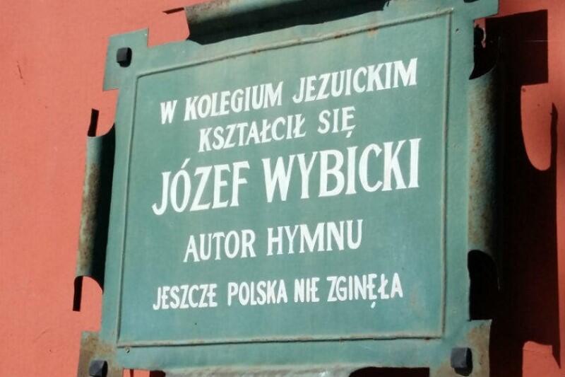 Pomalowana na zielono tablica z blachy, a na niej napis białymi literami: W kolegium jezuickim kształcił się Józef Wybicki autor hymnu Jeszcze Polska nie zginęła