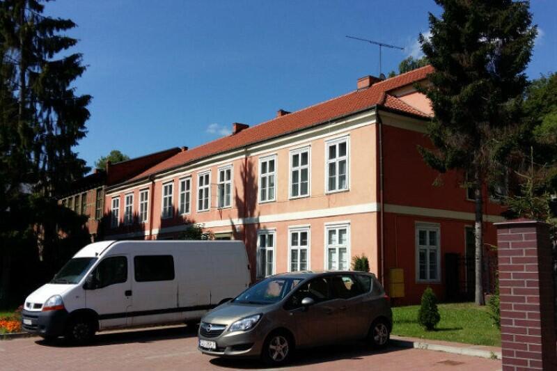 Duży i zabytkowy dwukondygnacyjny budynek ze spadzistym dachem, krytym dachówką. Na obu kondygnacjach znajdują się rządy równo rozmieszczonych obszernych okiem, których ramy pomalowane są na biało. Ściany budynku są koloru blado-pomarańczowego