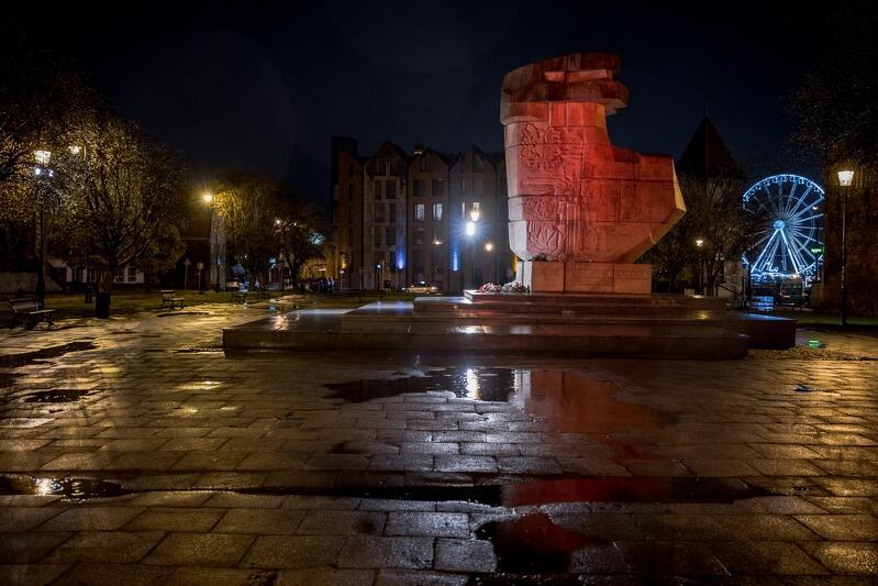 Ciemno, plac z kałużami wody. Na placu - trochę w oddali - pomnik Tym, co za Polskość Gdańska oświetlony na czerwono