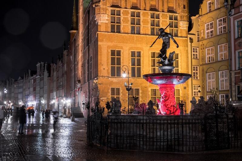 Ulica, na środku Fontanna Neptuna otoczona płotkiem. Cokół podświetlony na biało i czerwono. Za fontanną oświetlony na żółto wysoki budynek