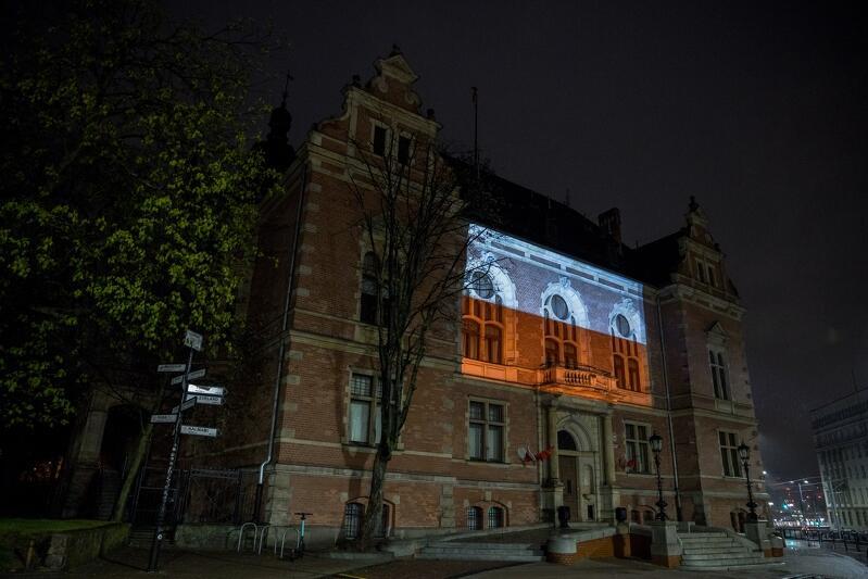Budynek Nowego Ratusza (siedziba Rady Miasta Gdańska) wieczorową porą. Ciemno. Na budynku iluminacja biało-czerwonej flagi