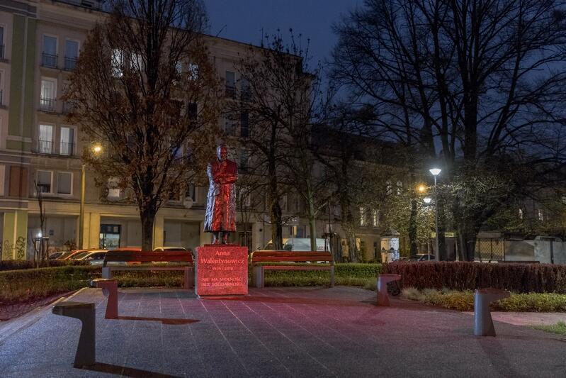 Wieczór, prawie ciemno. Plac chodnikowy, na nim pomnik Anny Walentynowicz podświetlony na czerwono. Za nim dwa drzewa, jeszcze dalej budynki wielopiętrowe
