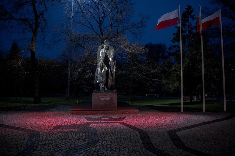 Wieczór, prawie ciemno. Plac w bruku, na nim pomnik marszałka Józefa Piłsudskiego podświetlony: cokół na czerwono, Marszałek na biało. Za nim zieleń - trawnik, krzewy, drzewa. Obok trzy maszty, na nich biało-czerwone flagi
