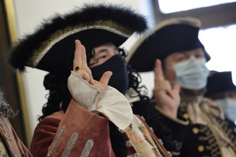 Dwóch mężczyzn ubranych w stroje z XVI wieku, mają podniesione prawe dłonie, trzy palce wyciągnięte ku górze. Na twarzach mają maseczki ochronne