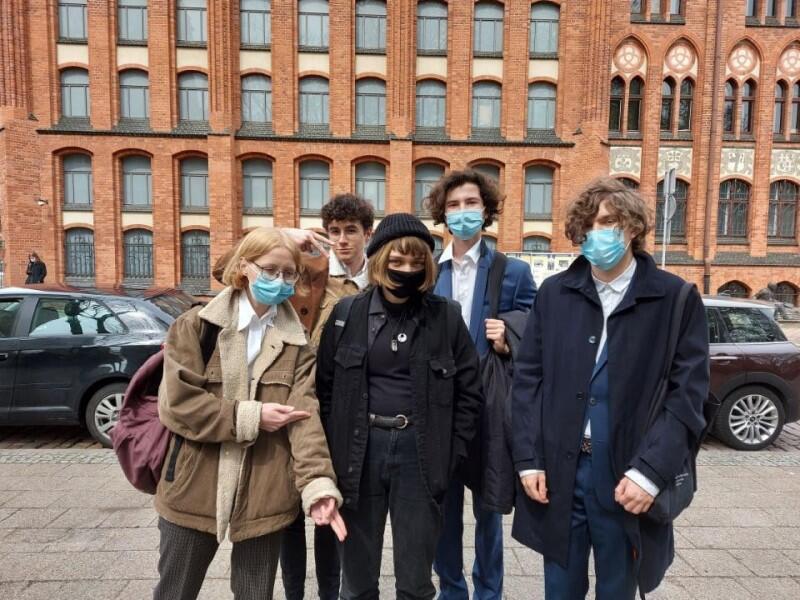 Pięcioro nastolatków, z przodu dwie dziewczyny ubrane w ciemne stroje z tyłu trzech chłopaków