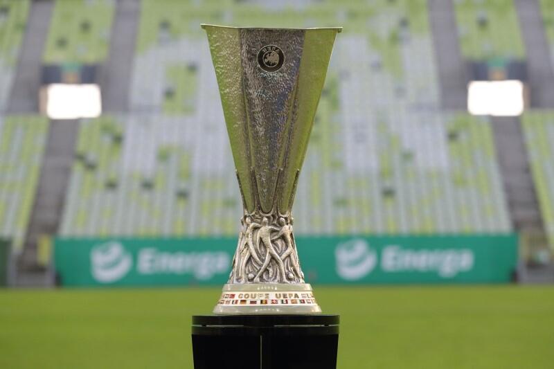Centralnie stoi metalowy puchar rozgrywek, jest w kolorze srebrnym. Kształtem przypomina rozszerzający się ku górze wysoki kielich. W górnej część wygrawerowany jest znak UEFA. U podstawy znajduje się opasująca puchar płaskorzeźba, która przedstawia wielu zawodników, walczących o piłkę. Pod ich nogami znajdują się w dwóch rzędach kolorowe flagi krajów, które są członkami UEFA oraz napis Coupe UEFA