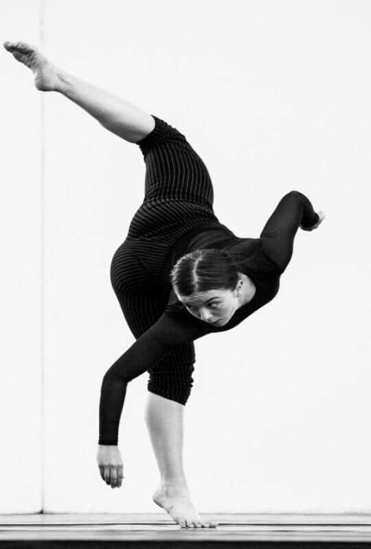 czarno białe zdjęcie, tańcząca młoda kobieta ubrana wczarny strój