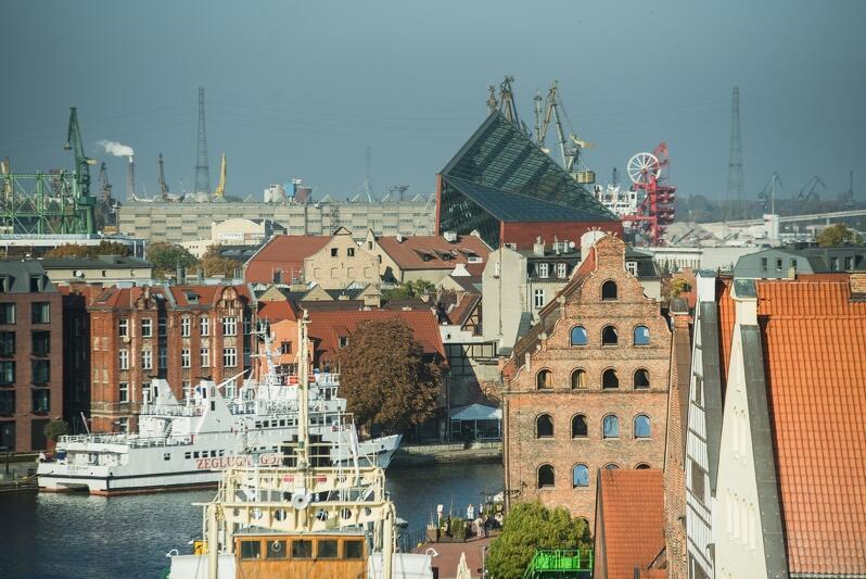 Fragment Gdańska nad Motławą, w tle wybija się Muzeum II Wojny Światowej, dalej stoczniowe żurawie