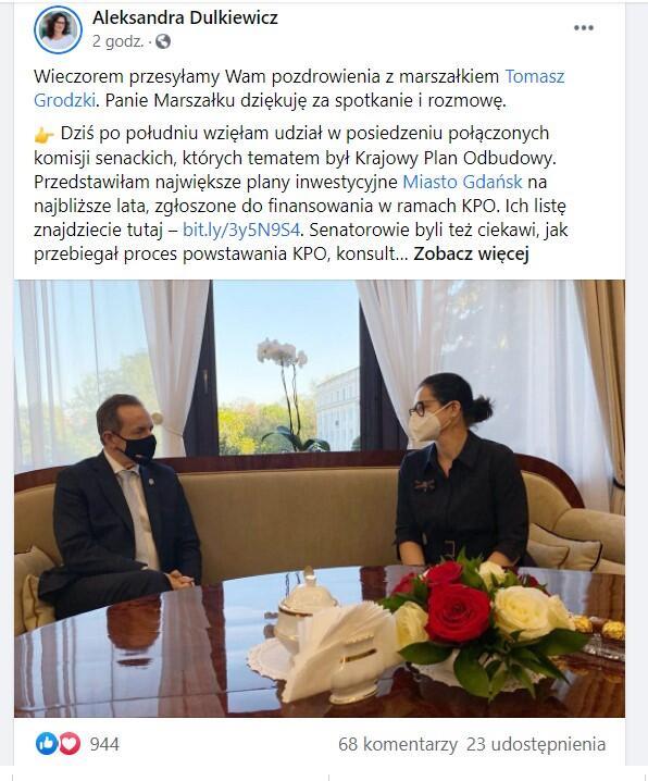 Marszałek Grodzki i prezydent Dulkiewicz siedzą za stołem, na sofie, i rozmawiają. Marszałek jest po lewej stronie, pani prezydent - po prawej. Oboje mają maseczki ochronne. Za nimi jest okno z widokiem na zieleń
