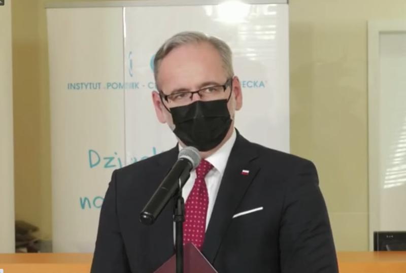 Un bărbat de vârstă mijlocie, cu părul gri, stă în fața microfonului cu steagul polonez în fundal