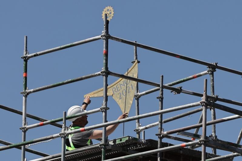 pokryta złotem chorągiew ustawiana jest przez robotnika w kasku na szczycie dachu