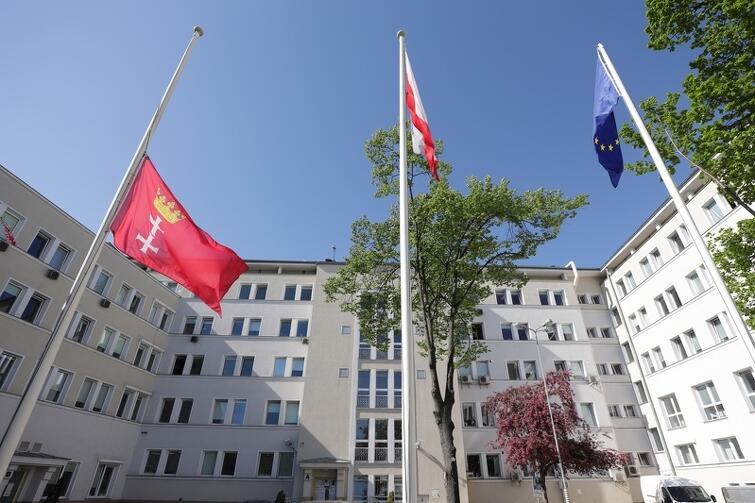 Trzy flagi na masztach otoczonych białymi budynkami. Jedna z nich - czerwona flaga Gdańska - opuszczona jest do połowy masztu