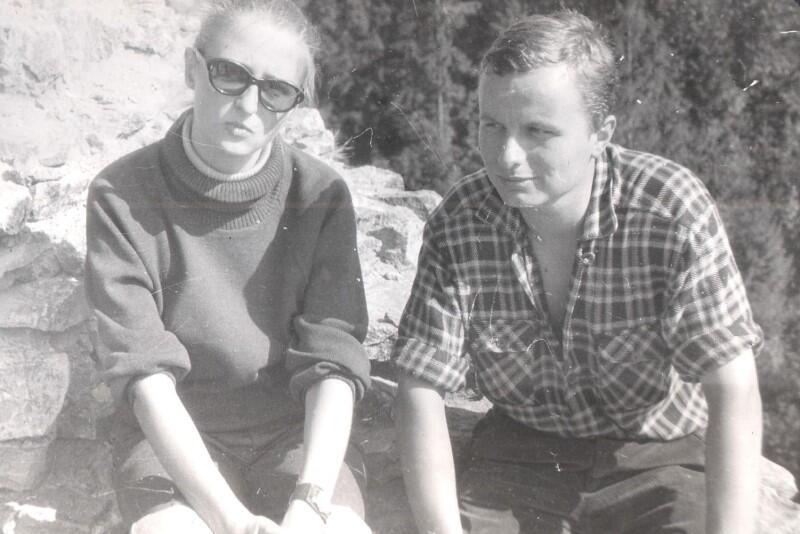 Zdjęcie czarno-białe: dwoje młodych ludzi w zbliżeniu, gdy siedzą obok siebie, na skale. On jest po prawej, ubrany w kraciastą koszulę, dość nisko rozpiętą pod szyją - zmęczony upałem patrzy nieco po skosie w lewo. Ona jest tuż po lewej, w okularach przeciwsłonecznych patrzy w obiektyw aparatu. Jest ubrana w ciemną bluzkę pod szyję, na ręce po prawej - znacznie powyżej nadgarstka, ma zegarek. Wokół jest typowa górska przyroda