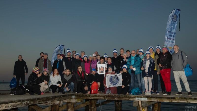 Zdjęcie wykonane późnym wieczorem, o zmroku. Grupa kilkudziesięciu osób - w większości w strojach sportowych, część w białych włóczkowych czapkach  - stoi lub kuca na pomoście nad Zatoką Gdańską. Centralnie ktoś trzyma zdjęcie Jacka Starościaka w stroju morsa, obok po prawej są dwie osoby, które trzymają niewielką białą flagę z niebieskim znakiem Sopockiego Klubu Morsów