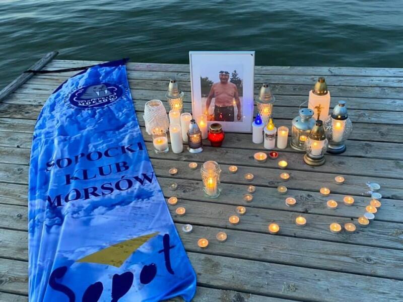 Wykonane pod wieczór zdjęcie pomostu nad wodą, na którym stoi zdjęcie Jacka Starościaka w stroju morsa - jest on na nim w czarnych kąpielówkach i białym czepku. Przed zdjęciem stoi kilkadziesiąt zniczy, część ułożona w kształt serca. Po lewej leży foliowa torba z napisem Sopocki Klub Morsów