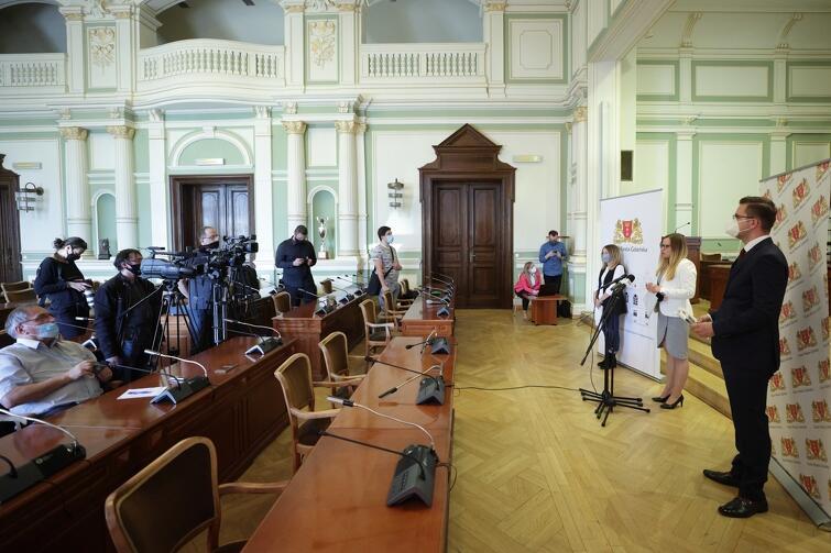 na zdjęciu widać trzy osoby po lewej, to przewodniczący klubów radnych, przed nimi stoją mikrofony, po drugiej stronie widać kilku dziennikarzy, w tym osoby z kamerami, a także fotoreporterów
