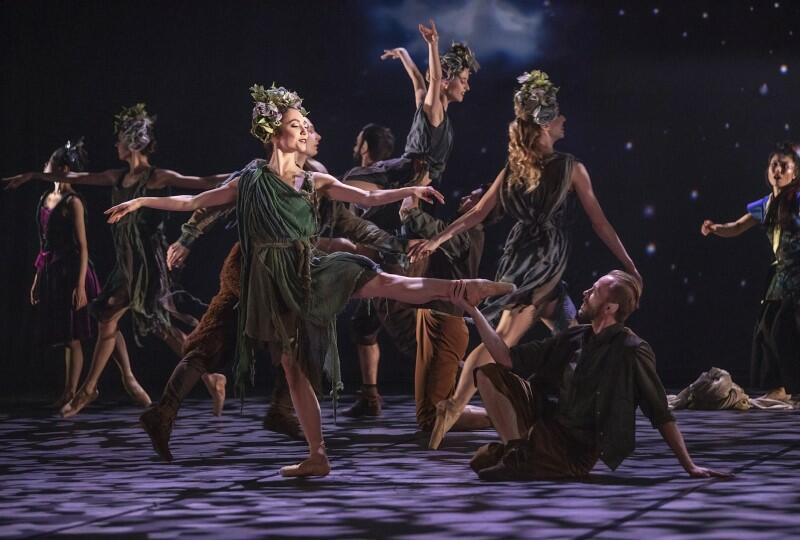 Tancerka, z wiankiem na głowie i w zielonej sukience, stoi w puentach na jednej nodze, drugą ma uniesioną. Tancerz w pozycji półleżącej wyciąga do niej rękę. W tle grupa tancerzy.