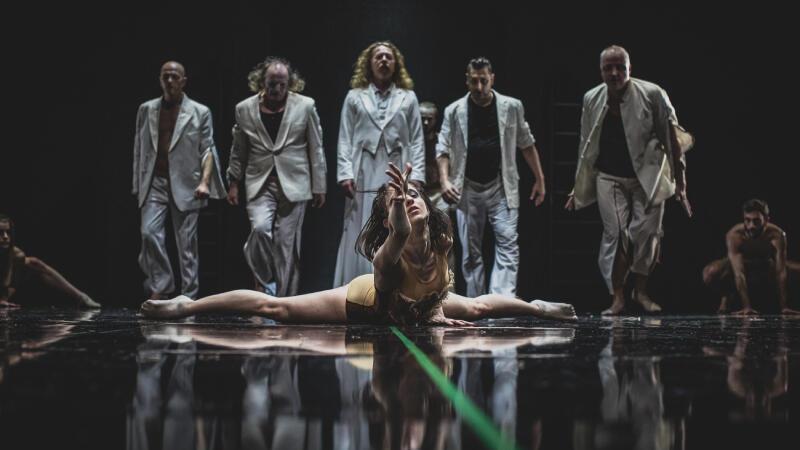 Tancerka w szpagacie pochyla się do przodu i wyciąga ramię w kierunku widza. W tle grupa tancerzy