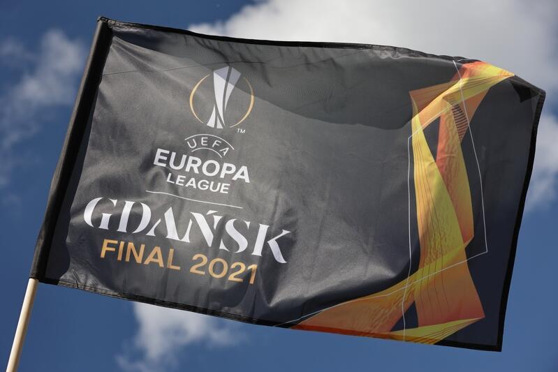 Flaga w czarno złotej tonacji kolorystycznej. Jest na niej centralnie wizerunek pucharu Ligi Europy oraz poniżej napis UEFA Europa League Gdańsk Final 2021