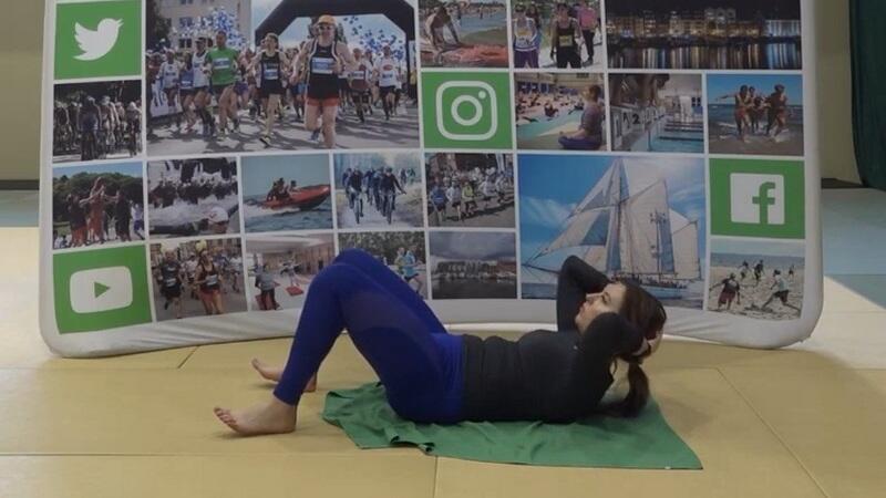 Młoda kobieta w stroju sportowym na sali gimnastycznej, leży na macie na plecach, nogi zgięte w kolanach, stopy na ziemi, dłonie za głową, głowa uniesiona do góry