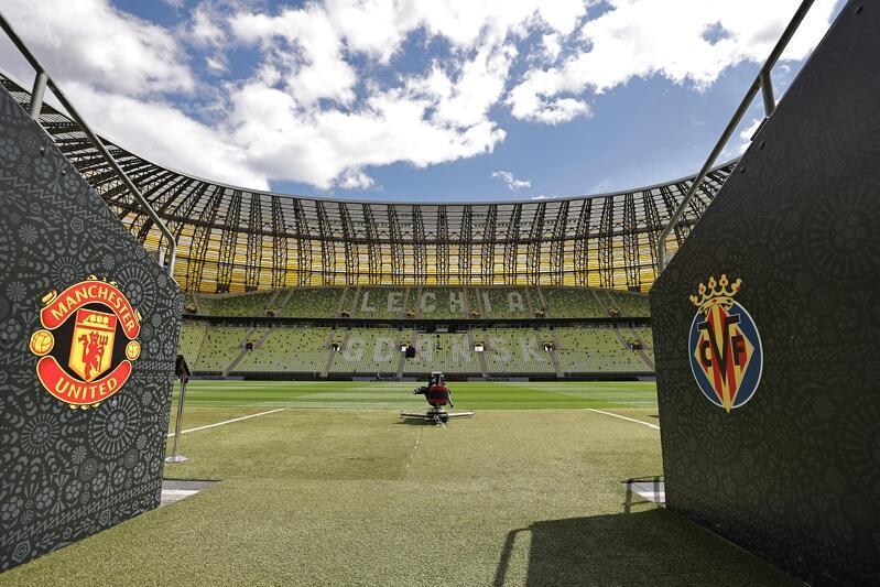 Wyjście na boisko. Widzimy dwie ściany po bokach, na których wymalowano dwa herby klubowe - po prawej czerwono-żółty Manchesteru United, po lewej żółto-niebieski Villarrealu CF. W głębi zdjęcia widoczne jest zielone boisko i dalej, za nim, trybuny