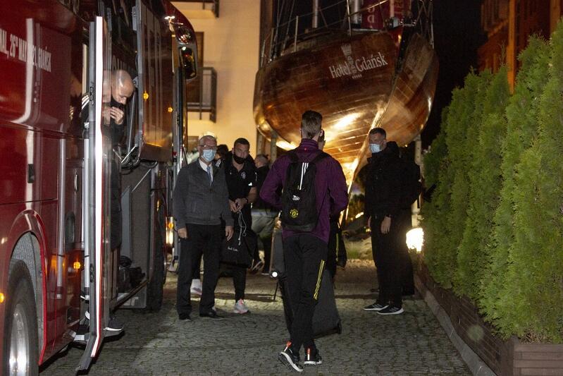 Za klubowego autokaru na szafarni wysiadł właśnie Sir Alex Ferguson - pan w maseczce, po lewej