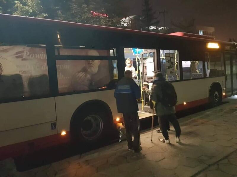 Wieczór, fragment oświetlonego w środku autobusu, przed drzwiami dwóch mężczyzn w średnim wieku