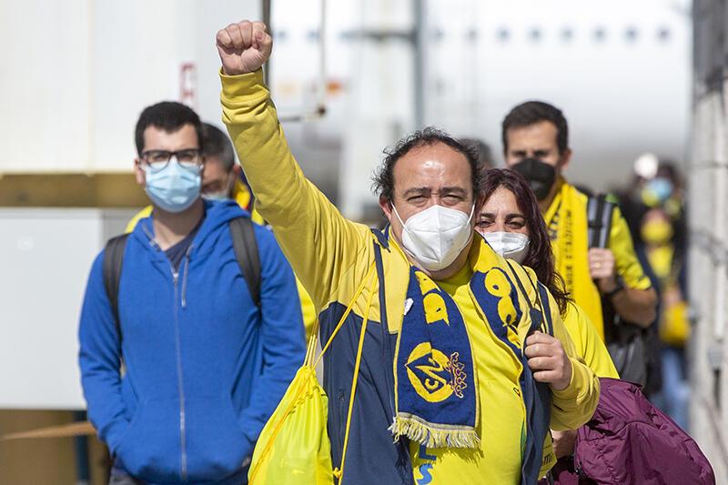 Mężczyzna w żółtej bluzie i szaliku Villarreal, w maseczce na twarzy idzie chodnikiem, prawa ręka uniesiona do góry z zaciśniętą dłonią. Za nim inni ludzie
