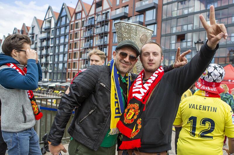 Dwóch mężczyzn stoi obok siebie, mają wyciągnięte do góry dłonie z palcami w kształcie V. Jeden w czapeczce w okularach ma szalik Villarreal, drugi - Manchester United. Za nimi wystaje fragment repliki pucharu Ligi Mistrzów. Po bokach inni ludzie, w tle budynki