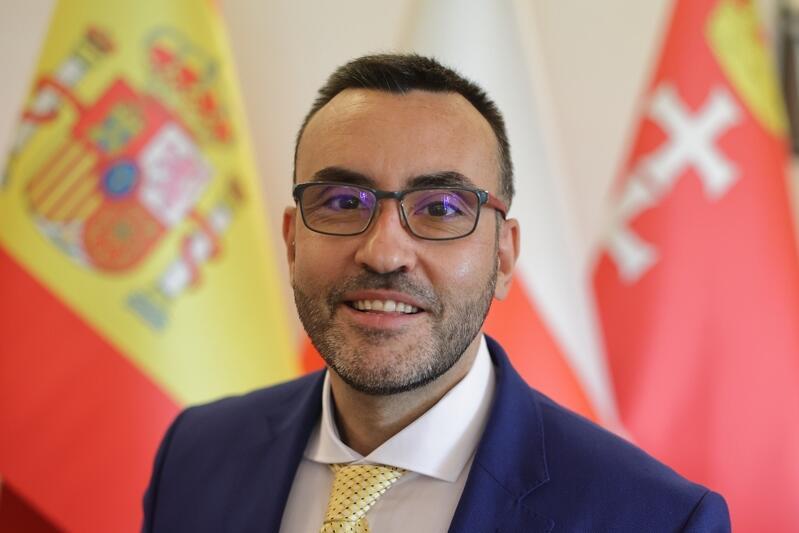 uśmiechnięty mężczyzna w średnim wieku, krótko ostrzyżony, w okularach i eleganckim garniturze. Pozuje na tle czerwono-żółtej flagi Hiszpanii
