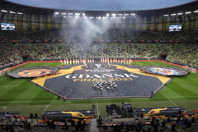 Boisko - widok z trybun. Na murawie rozstawione po bokach duże plansze z logo klubów Villarreal i Manchester United. W środku jeszcze większa plansza z napisami: EUROPA LEAQUE. GDAŃSK FINAL 2021. W tle trybuna, na której siedzą - gdzieniegdzie - ludzie